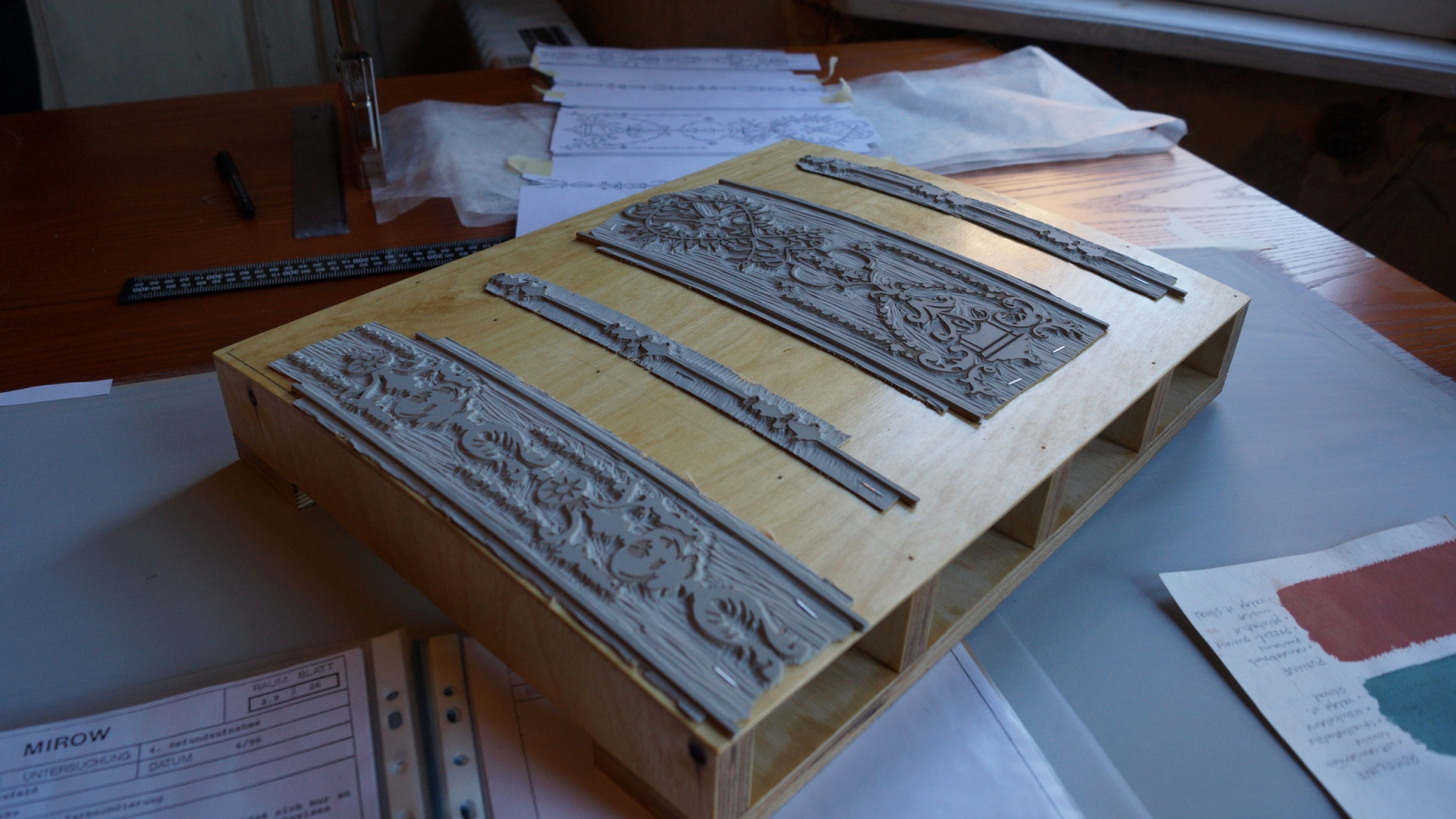ill 6. Printing block with three linocut pattern strips before printing the grey wallpaper.