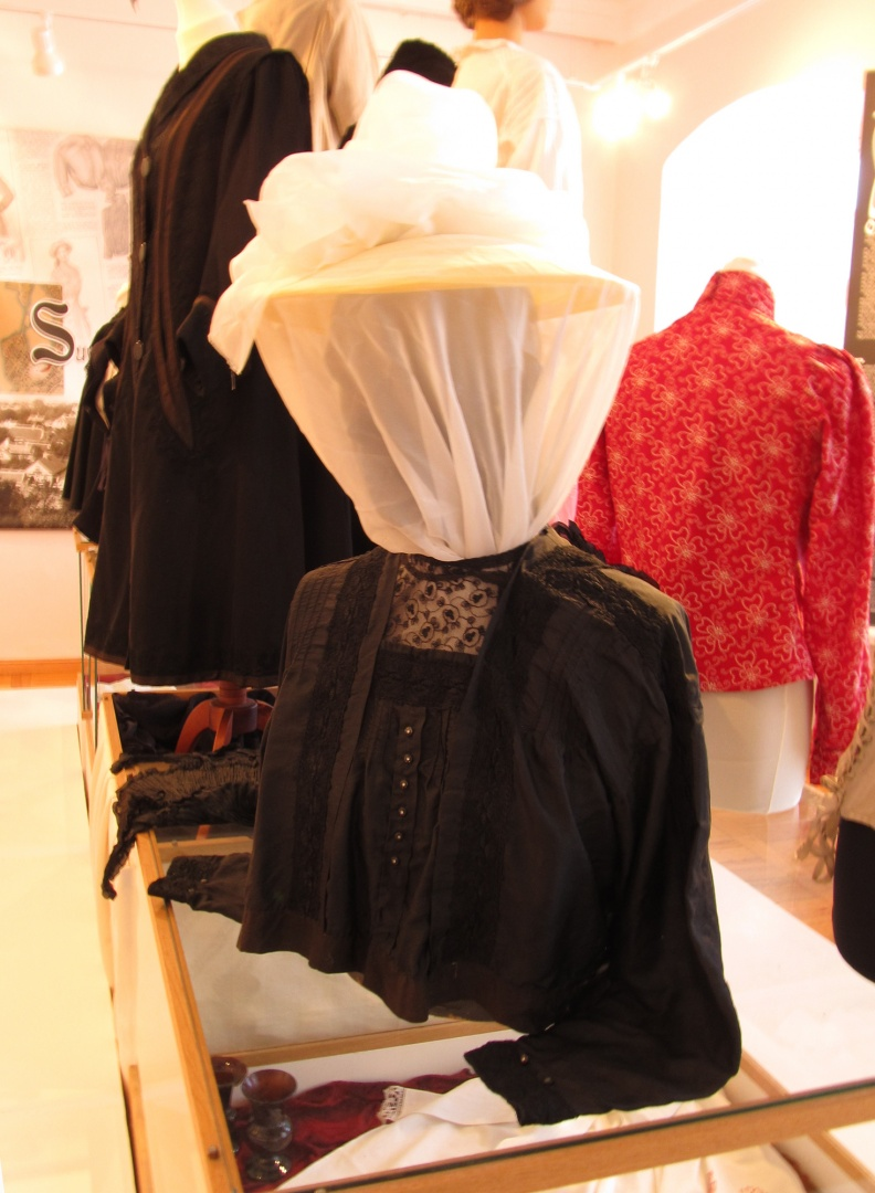 "ill 4. A crying need makes one resourceful – all the available mannequins, a male torso included, were taken into use. The blouse fitted all right, but the head had to be disguised. Thus a Chinese lantern's flat cover and curtain tulle were used to make a ""veiled"" bonnet."
