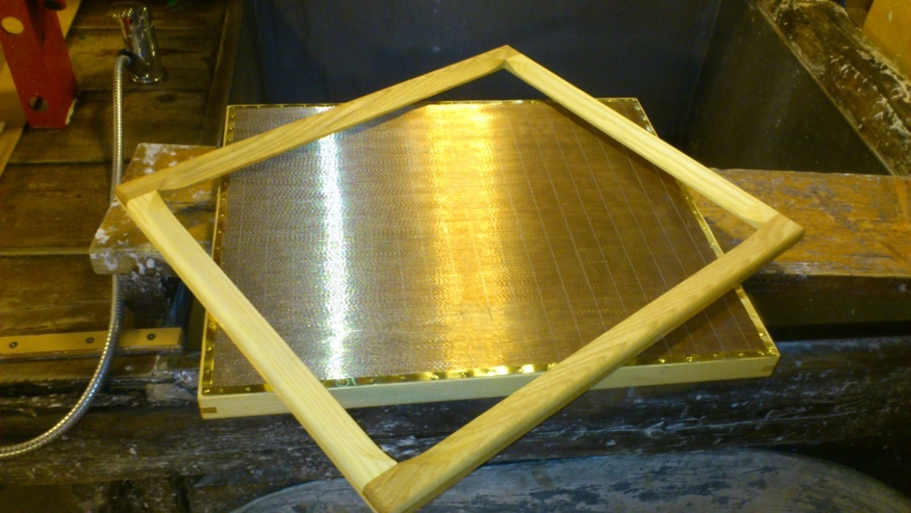 ill 1. The laid surface mould with a copper bronze mesh and a deckle to ensure size for the forming sheet.