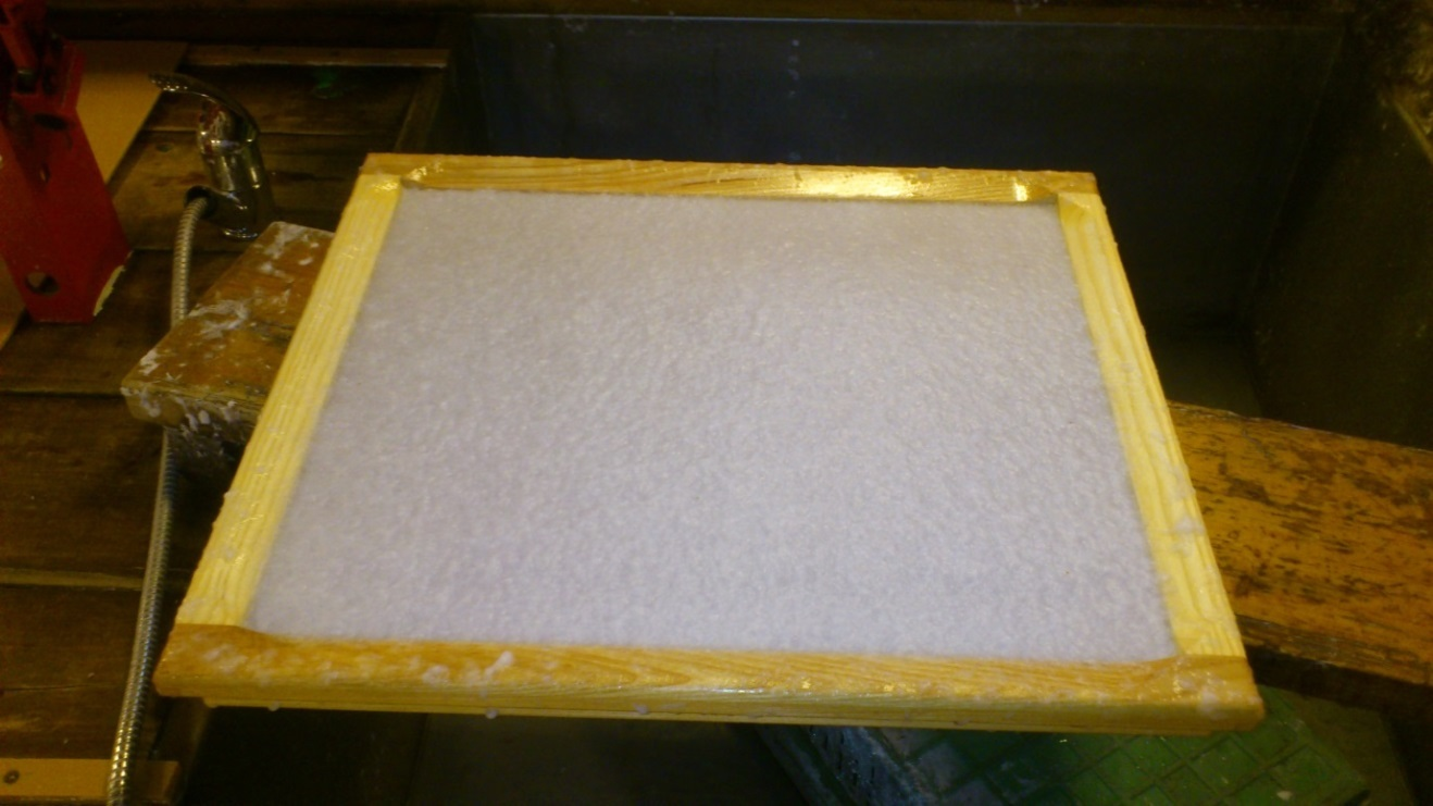ill 2. The pulp has been lifted from the vat and draining on the mould, fenced with a deckle.