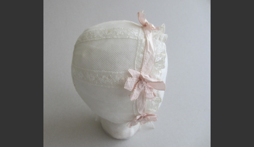 fig 61. A Varbla baby bonnet of tulle dating from the early 20th century and decorated with several pieces of lace and ribbon. Piret Tiismaa's private collection. Photo by Astra Kütt. The lace has been set in the way to imitate gores that narrow towards the nape. It need not be a cap for a baby-boy but still, this sort of traditional decoration reminds us of the cap of gores and it was generally used just for boys' caps.