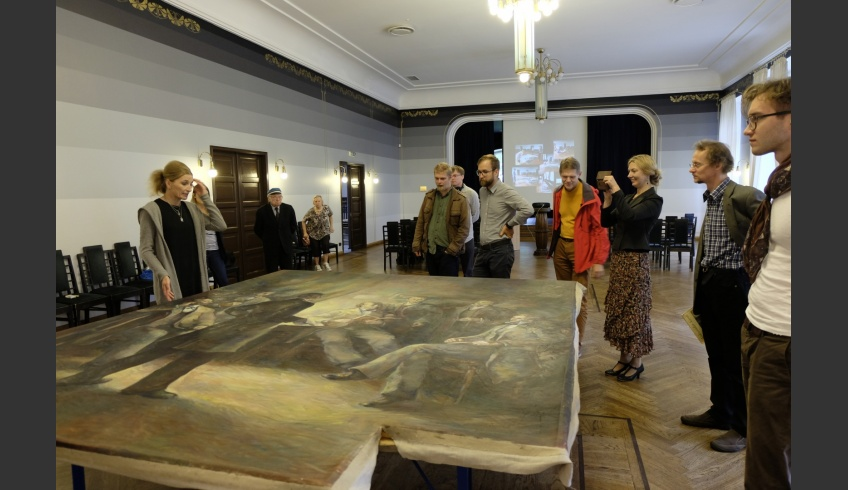 fig 12. Setting the restored painting Kalevipoeg Evenings on the supporting frame, witnessed by the public and its presentation in the EÜS hall (summer 2016). Photo: the Estonian Student Society