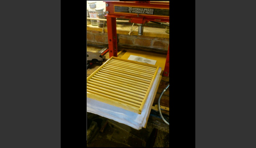 ill 7. Hydraulic press and laying of the last sheet. On the back side of the mould wooden ribs can be seen.