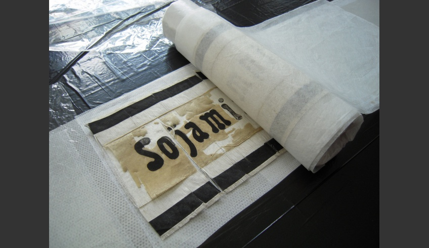 ill 17. The cleansed and stretched ribbon was placed onto the vacuum-table and glued with BEVA film on Hollytex fabric.