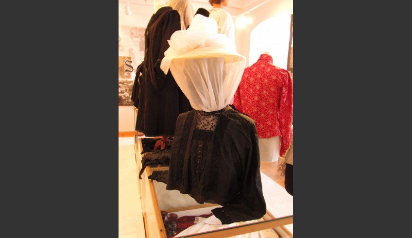 """ill 4. A crying need makes one resourceful – all the available mannequins, a male torso included, were taken into use. The blouse fitted all right, but the head had to be disguised. Thus a Chinese lantern's flat cover and curtain tulle were used to make a """"veiled"""" bonnet."""