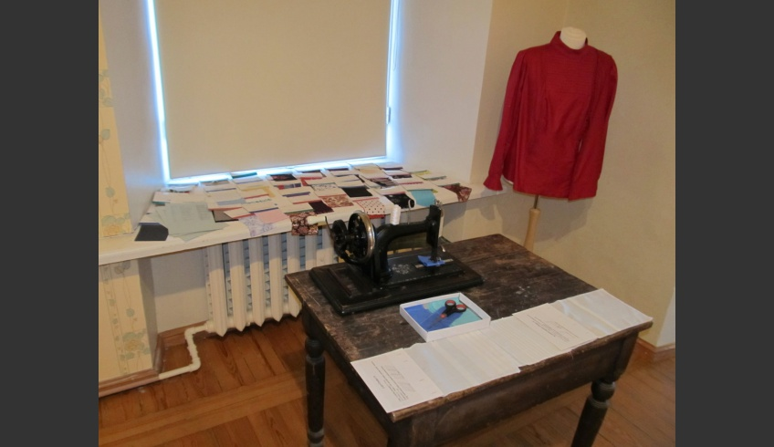 ill 6. An old sewing machine, a replica of a blouse and the fabric-ABC-book consisting of various examples on the windowsill.