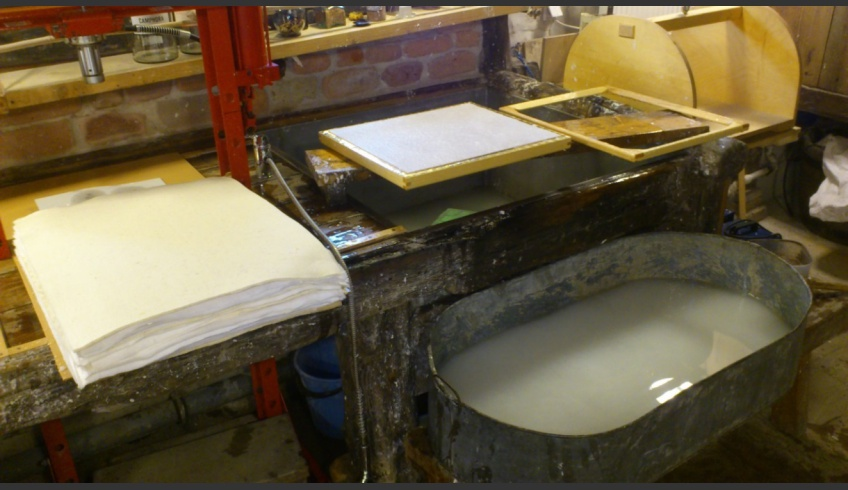 ill 4. When water stops dripping through the mesh, the newly formed sheet is laid upon the felt. In the picture a pile of fresh sheets and felts is seen on the left, laying front of the press.